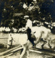 Photograph of Portus Acheson riding a horse, jumping