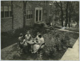Four women playing cards on the lawn at Chatham Village