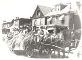 Parade participants in horse drawn hay wagon