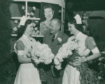 Flower Show official gives bouquets of Mamie Eisenhower carnations to nurses at 1953 Philadelphia...